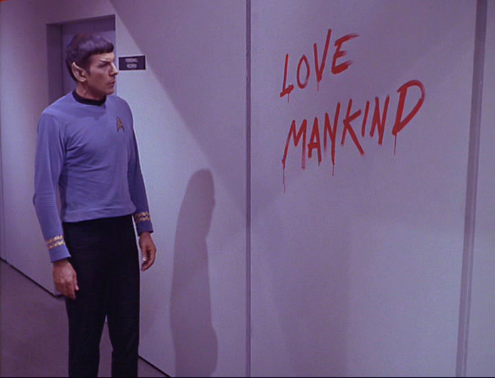 Spock observes a grafito: 'Love Mankind'.