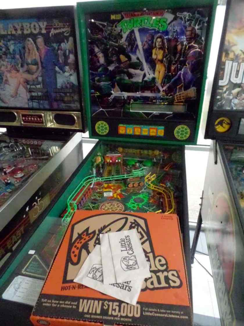 Sitting atop a Teenage Mutant Ninja Turtle pinball machine: a box of Little Caesar's pizza.